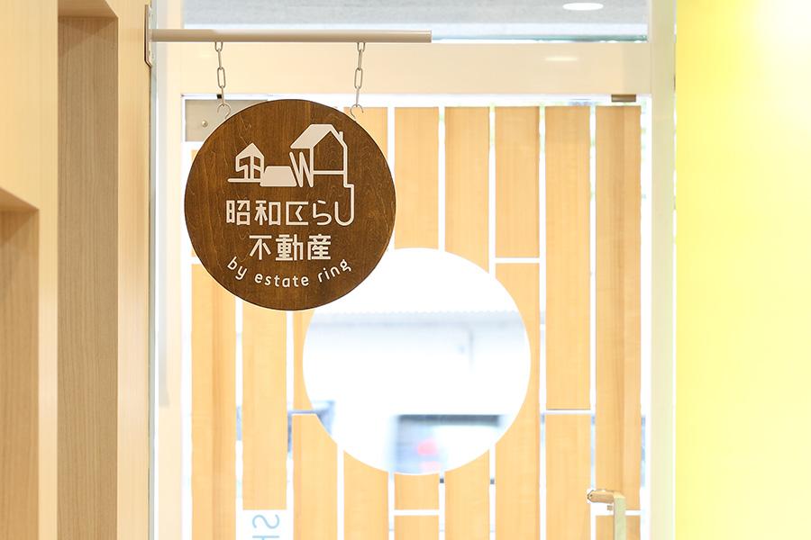不動産屋の窓越しのロゴ看板